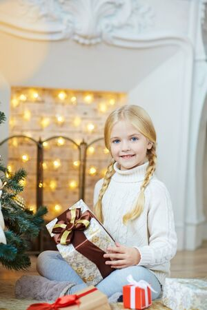 grandkid: Girl with present sitting on the floor by fireplace Stock Photo