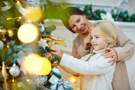 christmastime: Girl and her granny preparing firtree for Christmas Stock Photo