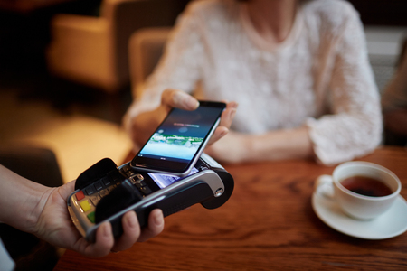 Modern person paying for her tea from smartphone Stock Photo