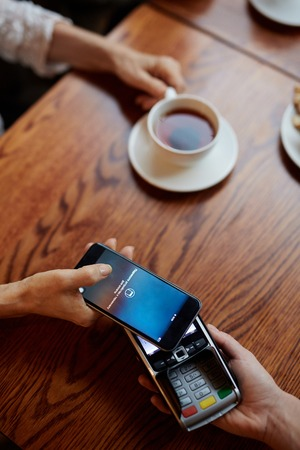 Modern money transfering system scanning cash from bank account to that of cafe owner