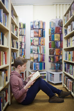 schooler: Serious guy sitting in library aisle with open book at leisure Stock Photo