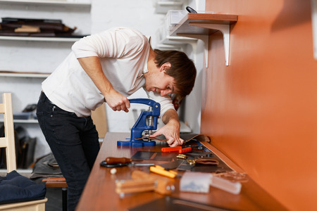 selfemployed: Self-employed tanner using special stapler to put together leather details