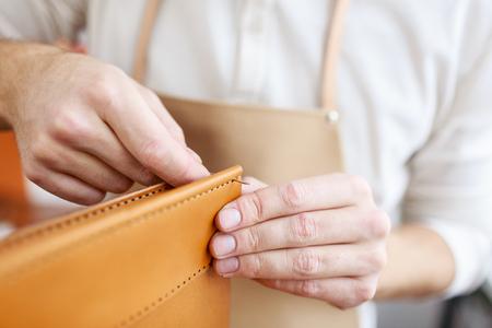 가죽 제품의 부분을 바느질하는 tanner 손