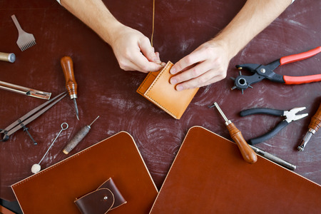 handtool: Human hands using handtool while producing leather item Stock Photo