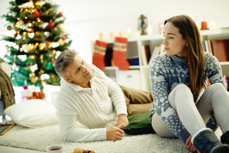 Husband and wife talking at home by Christmas tree photo