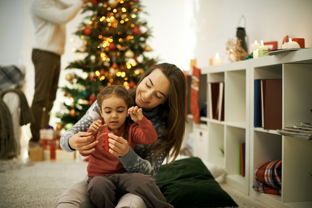 Mother and daughter sewing decorative toy to hang on xmas tree photo
