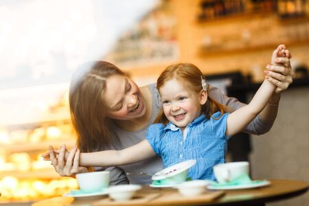 Woman and her cute daughter having fun in cafe Stock Photo