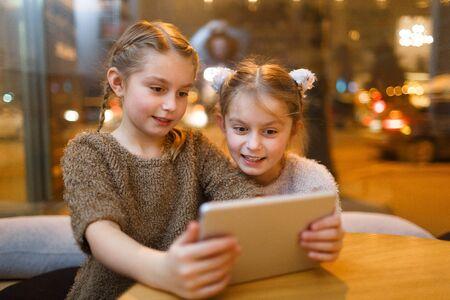 niñas gemelas: gemelos curiosos que miran algo sorprendente en la red