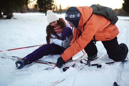 Jonge man helpt zijn vrouw tijdens het ski-ongeval