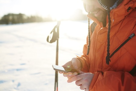 Skier messaging or reading sms in smartphone during training Stock Photo