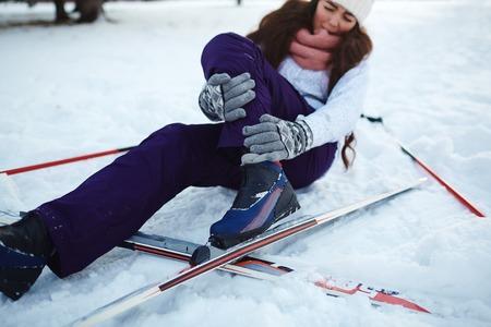 アクティブな女性がスキーのトレーニングの間に雪の上に倒れてください。 写真素材