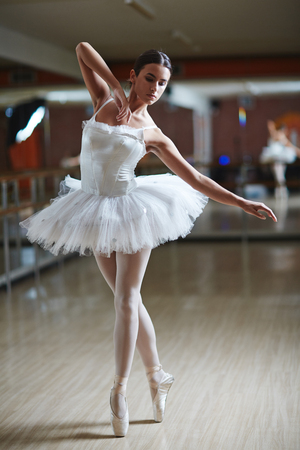 Ballet performer in white tutu dancing on stage