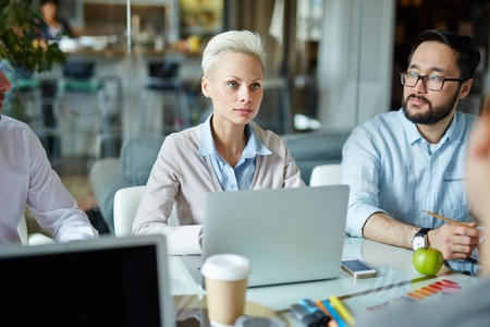 Young businesswoman listening to one of colleagues at meeting Stock Photo