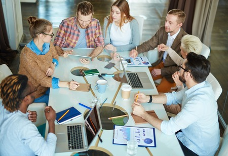 economists: Team of intercultural economists analyzing online sales Stock Photo