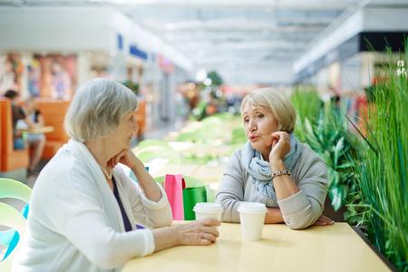 mujeres juntas: hembras de descanso que tienen una bebida y conversación después de hacer compras Foto de archivo