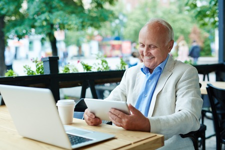Pleased Senior Looking at Tablet Screen Stock Photo