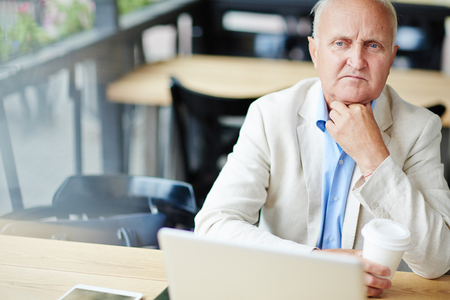 working attire: Thoughtful Senior Businessman in Cafe