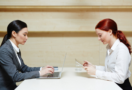 persona sentada: Pretty businesswomen working on computers