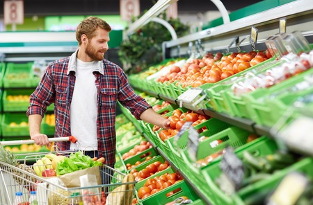 Man defining quality of tomato in supermarket