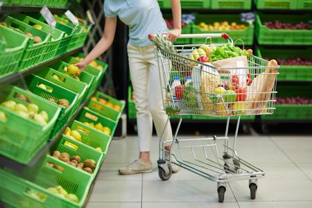 purchaser: Woman choosing lemons in supermarket