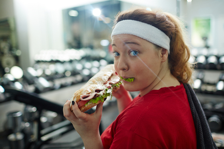 Oops I did it Again! Obese Woman Eating Sandwich in Gym Stok Fotoğraf - 72747406