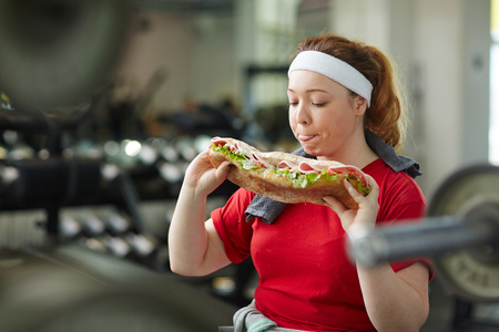fat food: Obese Woman Giving in To Food Temptation in Gym
