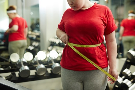 Overweight Woman Measuring Waist in Gym