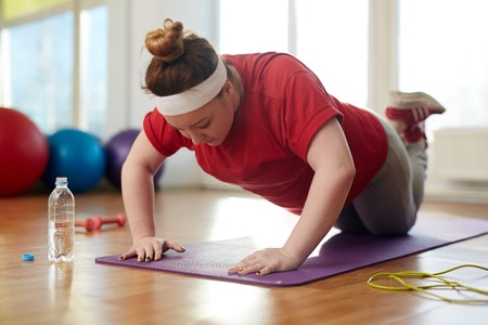 Obese Woman Doing Push Up Exercises to lose Weight Archivio Fotografico