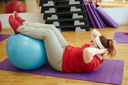 lose up: Obese Woman Doing Sit Ups Using Fitness Ball in Gym