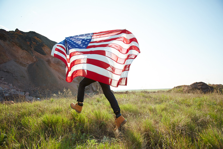 Young unrecognizable man running on green grass of mountainside waving big USA banner behind him lit by sunlight