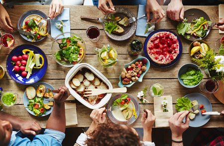 Friendly humans eating tasty dinner by festive table