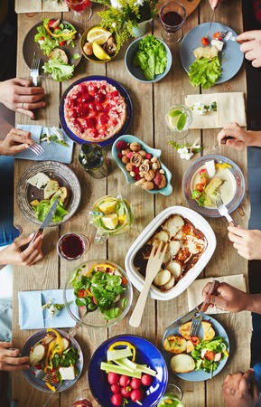 Hands of buddies eating vegetarian food by dinner Stock Photo - 72899866