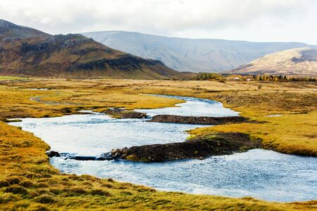Winding river on prairie with mounts on background