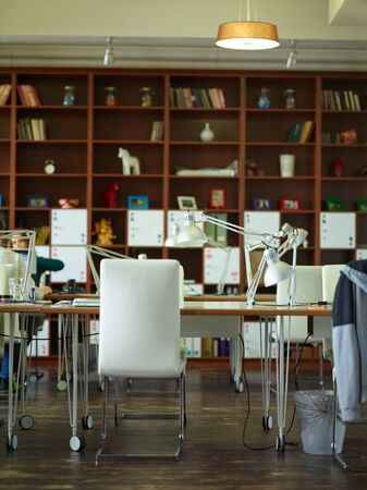 homelike: Working desks with lamps against tall bookcases in modern office room with interior in warm brown tones