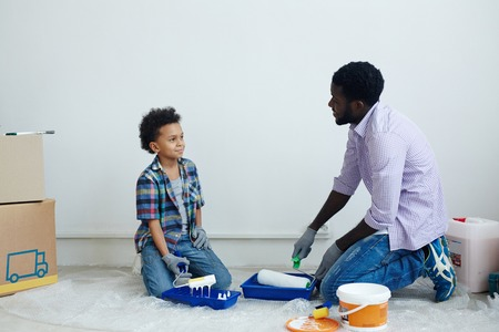 Father and his son going to paint walls in new flat