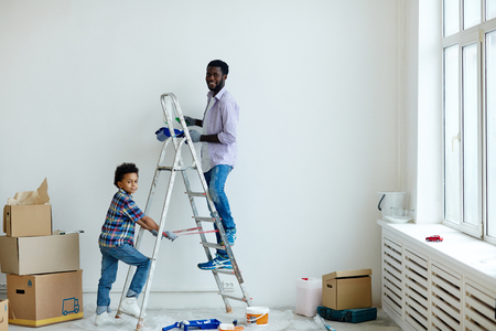 Father and his little son painting walls of new flat Stock Photo