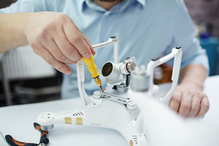 Closeup shot of unrecognizable man working on assembling new spy system using quadrocopter drone on table with different tools in modern workshop