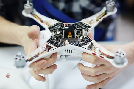 Closeup shot of male hands holding opened drone showing main circuit board and micro controller unit to camera against white table in workshop