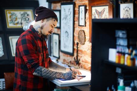ひげを生やした男のビーニー キャップとシャツ タトゥー サロンで創造的な飾りの絵を描く