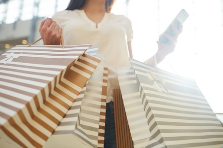shopper: Female shopper with striped paper-bags Stock Photo