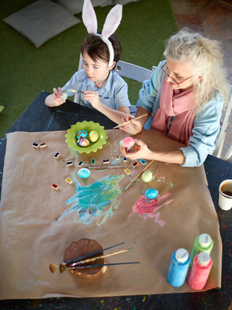 grandkid: Bunny boy and his grandmother painting Easter eggs Stock Photo
