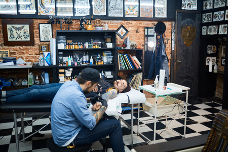 creative artist: Creative young man drawing tattoo on arm of client