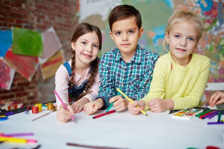 Friendly kids with crayons drawing on blank paper