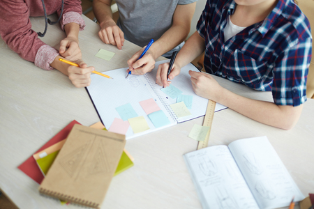 Over-view of group of students working by desk Stock Photo