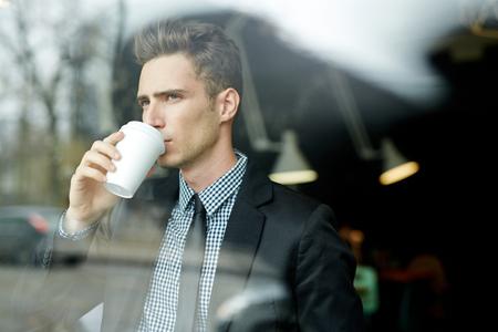 Giovane uomo d'affari con la tazza di carta