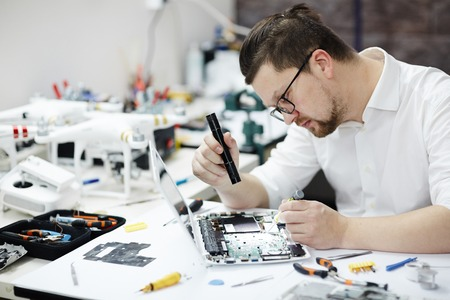 Man Checking Laptop for Broken Parts