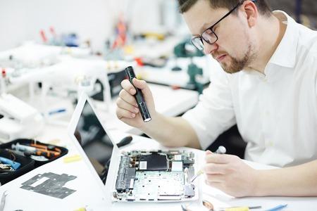 Modern Technician  Inspecting  Laptop for Broken Parts Stock Photo