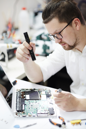 Modern Man Repairing Laptop in Workshop