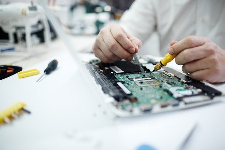 Closeup shot of unrecognizable man fixing circuit board in laptop using screwdriver and different tools on table in workshop