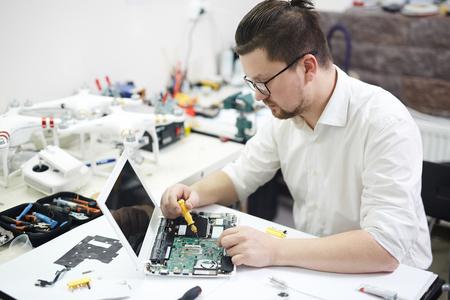 Focused Man Disassembling Electronics